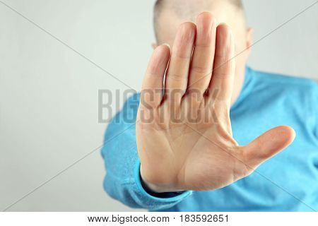 man doing stop gesture with the right hand