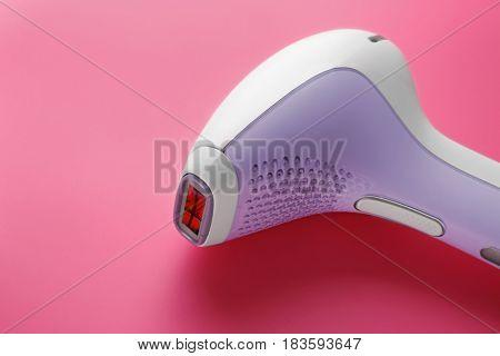 Modern laser epilator on color background