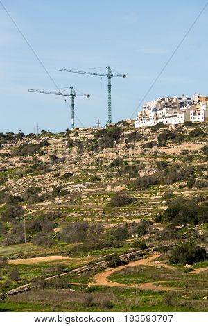 Cranes tower over Mellieha in the northern part of the island of malta. Construction in Malta severely threatens the little natural environment that is left on the island and tower cranes like these can be seen all over the country.