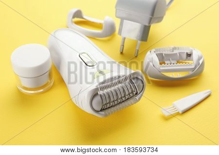 Modern epilator with attachments and cream on color background, closeup