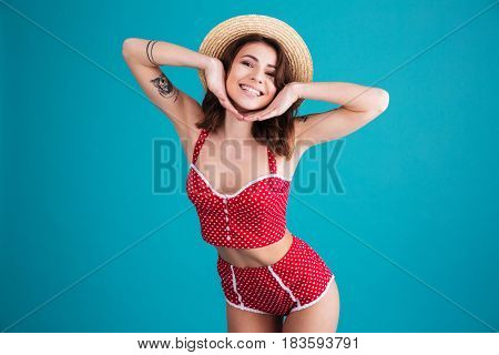 Smiling woman posing in studio and looking at the camera over blue background