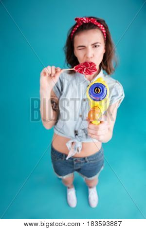Picture of young lady standing isolated over blue background. Looking at camera holding water gun and candy. Focus on water gun.