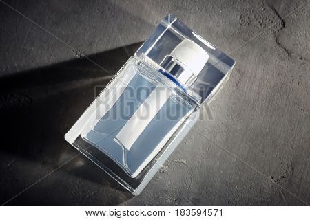Bottle of modern male perfume on grey textured background