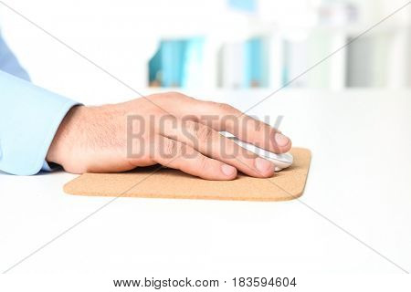 Hand of man working with computer mouse in office