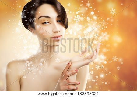 beautiful asian woman holds a product on snowy background
