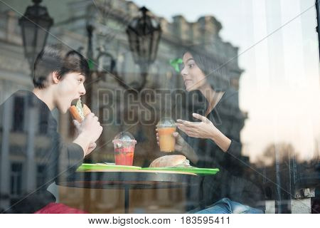 Photo of happy young man sitting in cafe with his sister drinking juice eating sandwich. Looking aside.