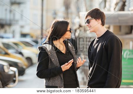Picture of young woman walking outdoors with her brother. Looking aside using mobile phone.