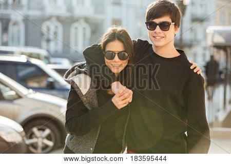 Image of young lady walking and have fun outdoors with her brother. Looking aside.
