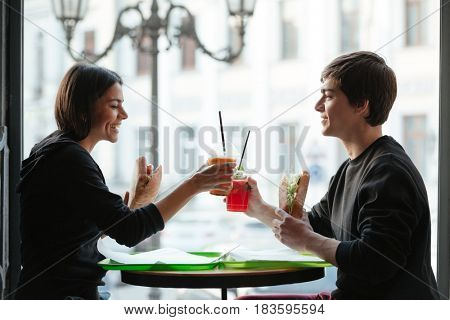 Photo of happy young man sitting in cafe with his sister drinking juice. Looking aside.