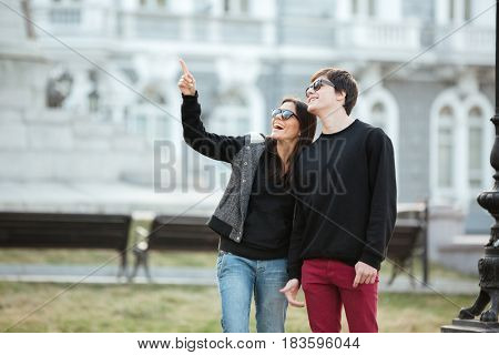 Picture of pretty young lady walking outdoors with her brother. Looking aside and pointing.