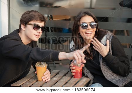 Image of happy young lady sitting outdoors with her brother drinking juice. Looking aside and pointing.