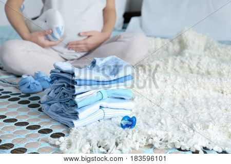 Pile of baby clothes and pregnant woman on bed