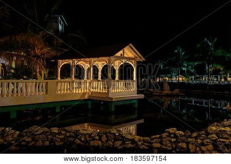 Cayo Coco island, memories Caribe hotel, Cuba, June 26, 2016, gorgeous amazing, inviting view of Memories Caribe hotel grounds with cozy gazebo lighted with various warm lights, reflected in water at evening time in tropical garden