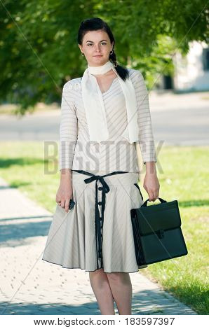Smart and confident young woman striding through summer park with black briefcase
