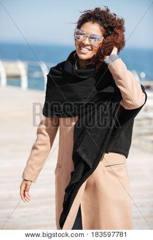 African smiling woman swearing glasses walking near sea