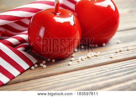 Delicious toffee apples with striped napkin on wooden background