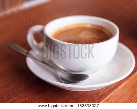 Hot coffee in a white cup with a spoon