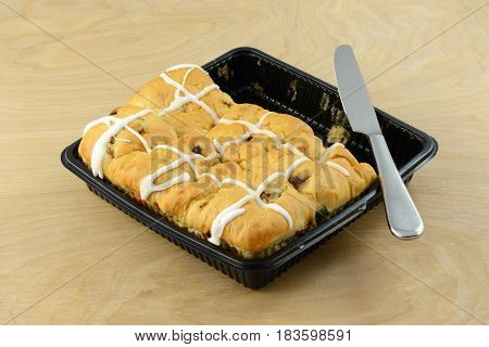 Hot cross buns in plastic container and knife with some buns already removed and eaten