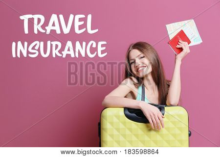 Travel insurance concept. Young woman with suitcase, passport and map on color background