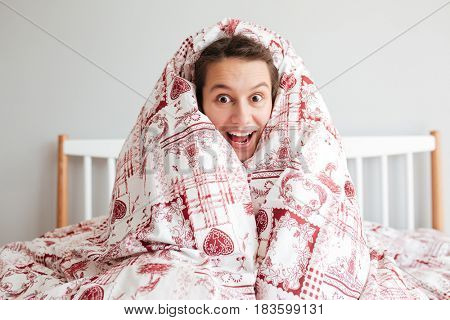 Portrait of cheerful young woman sitting in blanket in bedroom