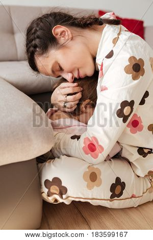 Little child hiding in mother's hugging at home