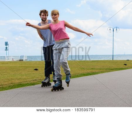 Young Couple Rollerblading Together