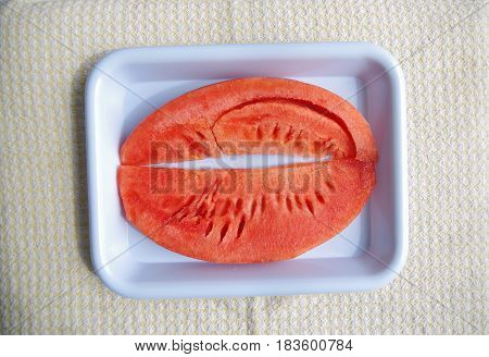 Watermelon slices with the seeds removed on a blue plastic tray.