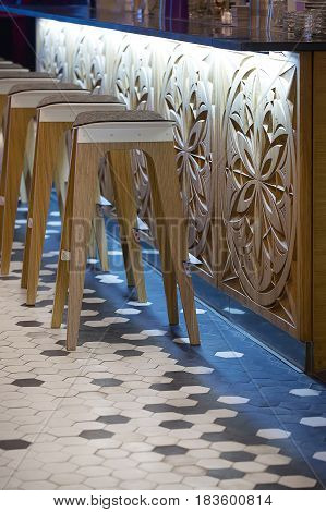 Several wooden stools on the carved bar rack background in the modern cafe. There are black and white tile on the floor and glowing lamps under the rack. Closeup. Vertical.