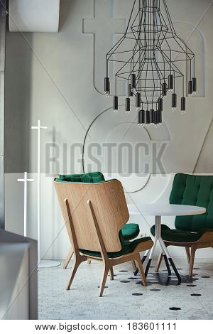 Three green armchairs around white round table in the cafe in a modern style with light walls. There are hanging black lamps over the table and black and white tiles on the floor. Closeup. Vertical.