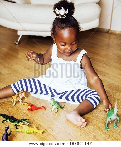 little cute african american girl playing with animal toys at home, pretty adorable princess in interior happy smiling, lifestyle real people concept close up