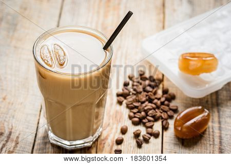 iced coffee with beans for cold summer drink on wooden table background