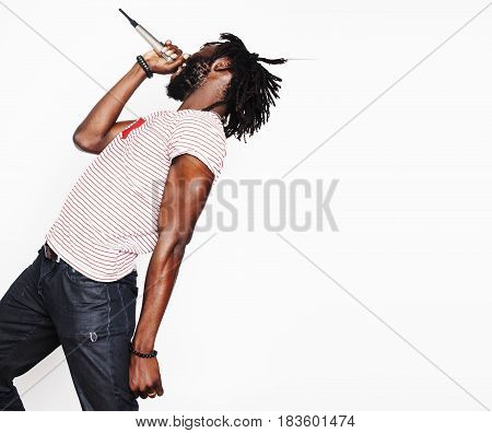 young handsome african american boy singing emotional with microphone isolated on white background, in motion gesturing close up