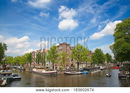 AMSTERDAM - JULY 10: Canals of the Amsterdam city on July 10, 2016 in Amsterdam, Netherlands.The historical canals of the city and traditional dutch houses is one of the main attractions of Amsterdam.