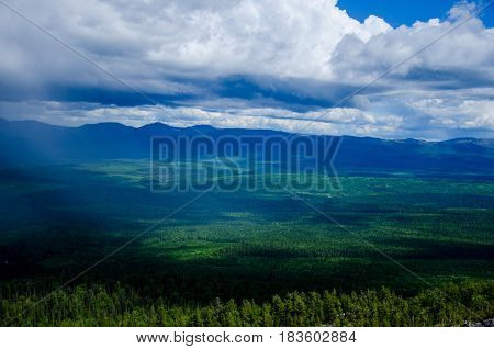 Green plain beneath the cloudy skies from the top of mountain