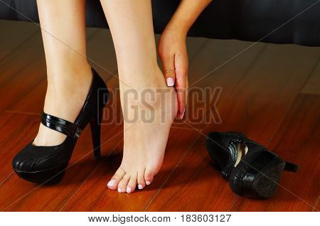 High heels shoe feet pain. The woman took off her shoes from fatigue in the legs