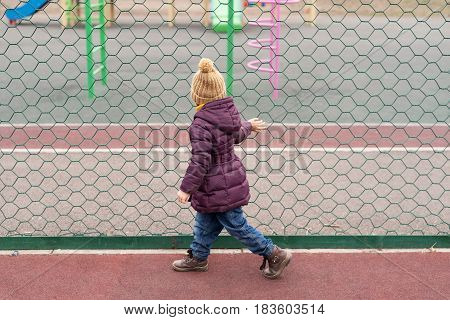 Little girl in a violet coat and a beige woolen hat walking alone the green mesh and looking at the playground.