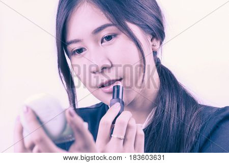 Asian woman applying makeup using lipstick for beauty concept isolated on white background.