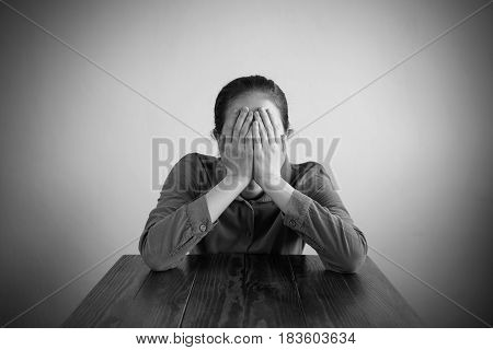Depressed woman sitting at a table covering her face with her hands. Manipulated black and white image, vignette is added.