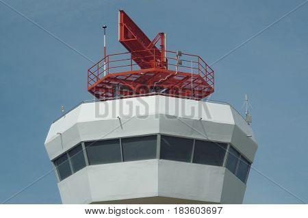 Radar dish on top of an airport control tower.