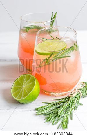 fitness cocktail in glass with cut lime and fresh rosemary on white table background