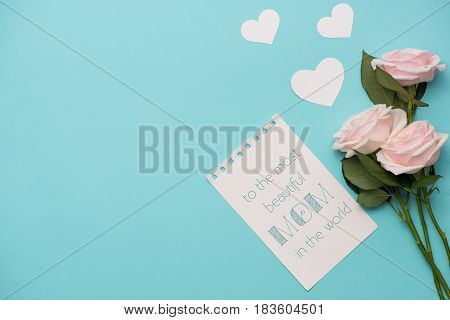 Mother's Day concept. Pink roses with gift box and lipstick. Open notebook for copy space.