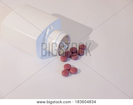 A Generic White Bottle With Red Tablet Pills Poured Out Of It Dispensed On White Background
