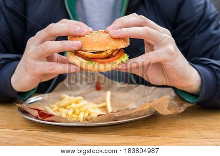 close up view of man's hands with american burger. Eating fast food in street cafe