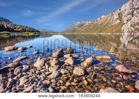 Picturesque summer in Argentina. The concept of exotic and extreme tourism. Lake with a stony pebble bottom at the famous resort of Bariloche