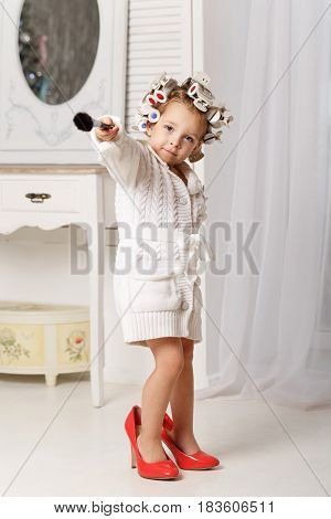 Little girl fashionista. A girl in a curler a robe and red high-heeled shoes is holding a makeup brush. Little coquette posing. Human emotions. As an adult.