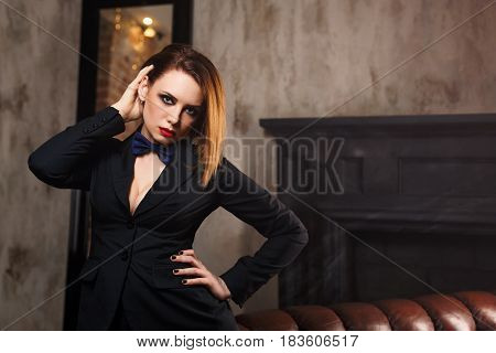 Young attractive girl in a butterfly jacket and tie. Femme fatale. The artsy fashion. Evening makeup smokey eye. She adjusts her hair