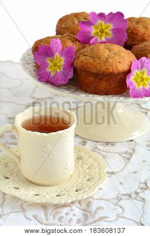 Fresh baked banana muffins with tea in pretty cup with flowers. Vertical format with shallow depth of field.