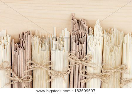 Different bundles of raw asian noodles close up on beige wooden board background top view.