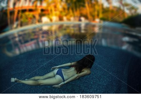 Woman swims underwater in the pool in lush tropical garden