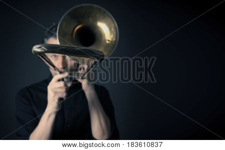 Dark portrait of a musician with a trombone selective focus and space for text